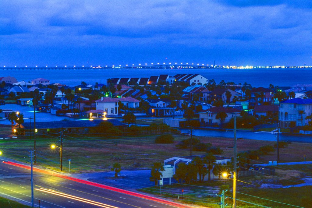 South Padre Island Night Shot of Beach Homes and Bay Inlet and Port Isabel, TX in the distance; CQ Integrative Health Visiting Patients